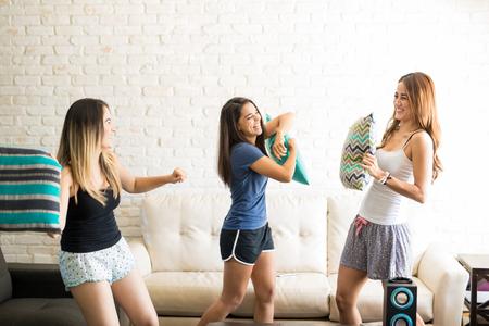 Foto de Group of young female friends in pajamas having fun during a pillow fight at home - Imagen libre de derechos