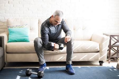 Foto de Hispanic man in his 50s sitting on sofa in living room and exercising, lifting dumbbells. - Imagen libre de derechos