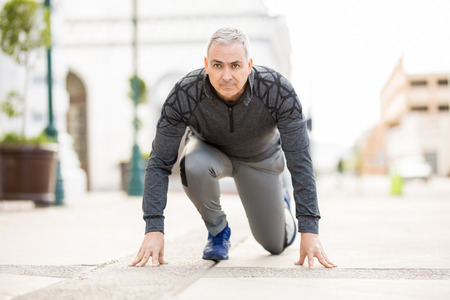 Photo for Portrait of mature Hispanic man in the ready position before going for a run in the city - Royalty Free Image