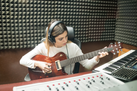 Photo for Woman with headphones playing guitar for preparing new sound track in soundproof recording room - Royalty Free Image