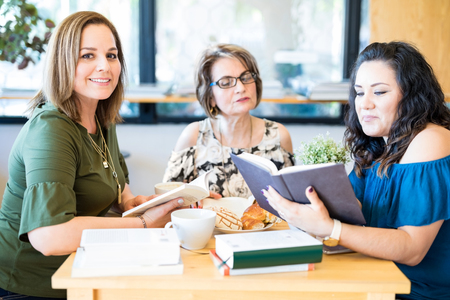 Photo pour Portrait of attractive young hispanic woman with friends reading book at a book club - image libre de droit