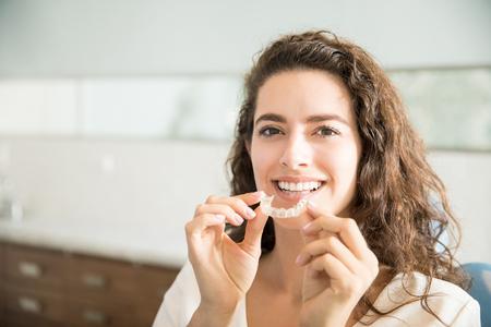Photo pour Portrait of beautiful patient holding orthodontic retainers in dental clinic - image libre de droit