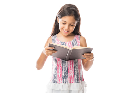 Photo pour Little smart girl holding a book and reading it while standing against white background - image libre de droit
