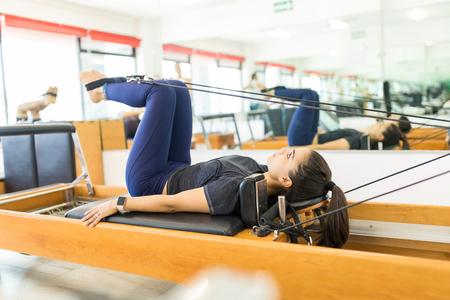 Foto de Side view of flexible female using pilates reformer machine in gym - Imagen libre de derechos