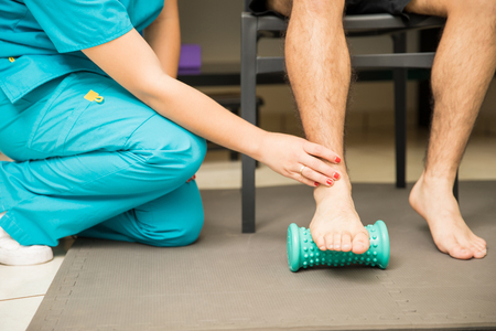 Photo pour Low section of female therapist assisting patient to use foot roller for plantar fasciitis and pain relief in hospital - image libre de droit