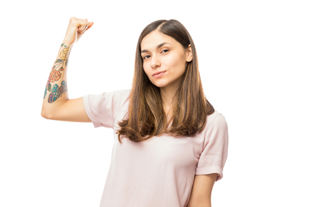 Foto de Confident young woman flexing her biceps against white background - Imagen libre de derechos