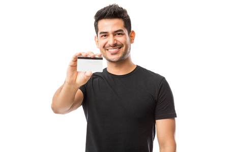 Photo pour Attractive guy promoting credit card while standing against white background - image libre de droit