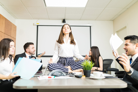 Photo for Young businesswoman meditating in lotus position while colleagues yelling during negotiation in office - Royalty Free Image
