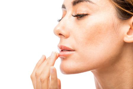 Photo pour Sexy female model moisturizing her lips against white background - image libre de droit