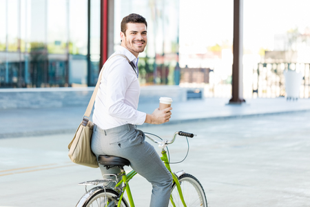 Photo pour Portrait of administrator smiling while holding disposable cup and riding cycle in city - image libre de droit