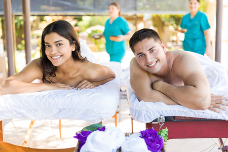 Photo for Portrait of smiling young partners lying on massage beds at healthcare center during vacation - Royalty Free Image