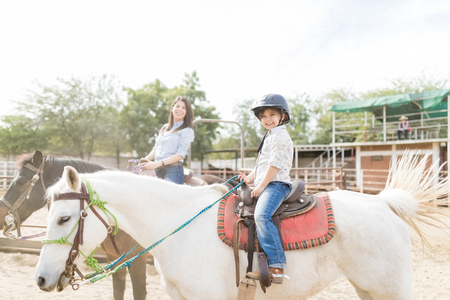 Photo pour Innocent female child enjoying horseback riding with mother at ranch - image libre de droit