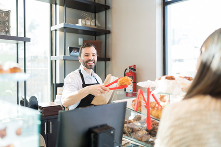 Photo pour Good looking salesman smiling while packing bread in paper bag for customer at store - image libre de droit