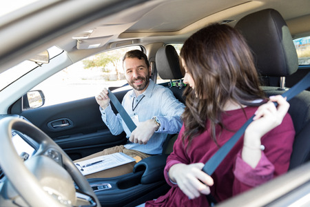 Photo for Smiling driving instructor teaching woman to fasten seatbelt of car - Royalty Free Image