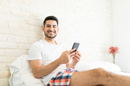 Photo pour Portrait of attractive man installing new app on smartphone in bedroom - image libre de droit