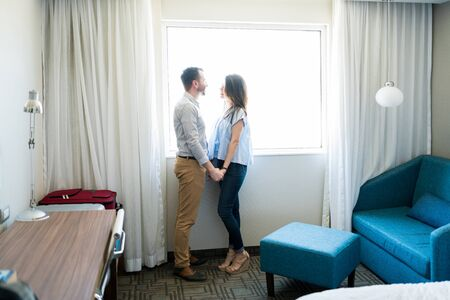 Foto de Full length side view of mid adult newlywed couple holding hands and talking while standing by window in room - Imagen libre de derechos