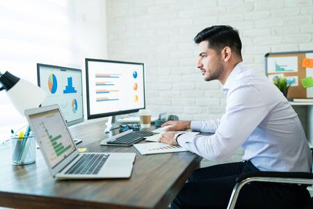 Photo for Side view of young attractive businessman studying charts on computer while working at home - Royalty Free Image