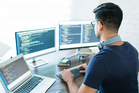 Photo for Rear view of young Latin software developer programming while working from home - Royalty Free Image