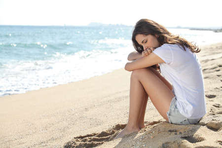 Portrait of a worried girl sitting on the beach with the sea in the background