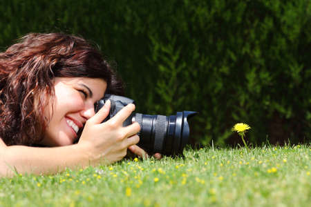 Photo pour Profile of a beautiful woman taking a macro photography of a flower on the grass in a park - image libre de droit