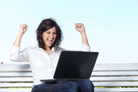 Photo pour Euphoric businesswoman with a laptop sitting on a bench with the sky in the background                 - image libre de droit