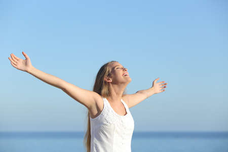 Photo pour Beautiful blonde woman breathing happy with raised arms with the sky in the background - image libre de droit