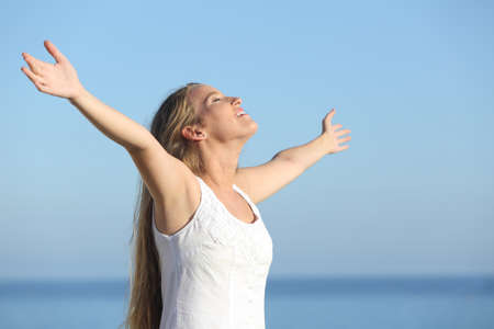 Photo pour Attractive blonde woman breathing happy with raised arms with the sea in the background              - image libre de droit