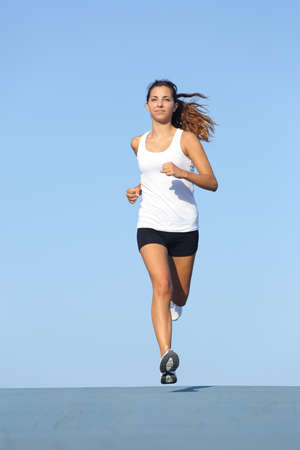 Front view of a beautiful sportswoman running towards camera with the blue sky in the background