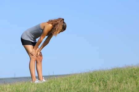 Foto de Fitness woman tired resting on the grass with the sky in the background - Imagen libre de derechos