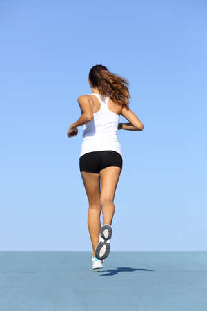 Back view of a fitness woman running on blue with the horizon in the background