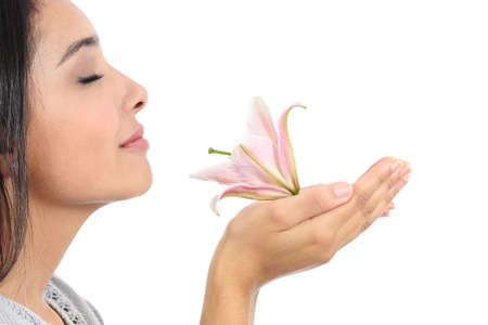 Foto de Close up of a beautiful woman profile smelling a pink flower  - Imagen libre de derechos