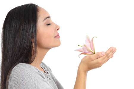 Foto de Side view of an arab woman smelling a flower isolated on a white background - Imagen libre de derechos