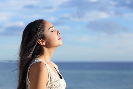 Foto de Profile of a beautiful arab woman breathing fresh air in the beach with a cloudy blue sky in the background - Imagen libre de derechos
