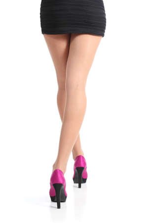 Back view of a woman legs walking with fuchsia high heels isolated on a white background