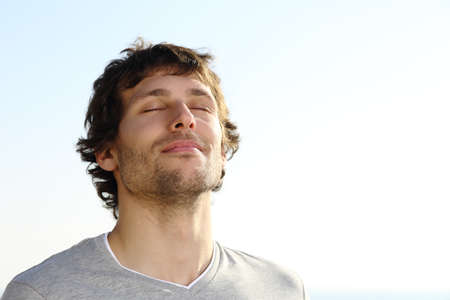 Foto de Attractive man breathing outdoor with the sky in the background              - Imagen libre de derechos