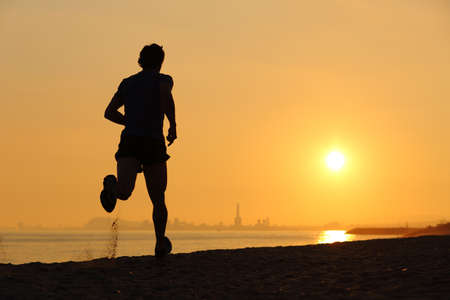 Photo pour Backlight of a man running on the beach at sunset with the horizon in the background - image libre de droit