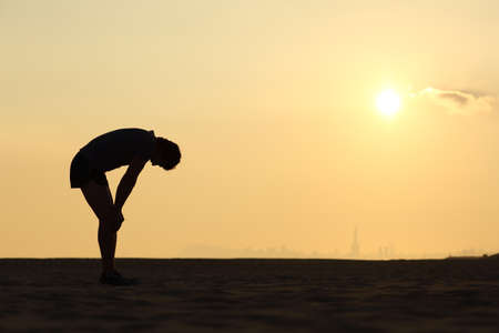 Photo pour Silhouette of an exhausted sportsman at sunset with the horizon in the background - image libre de droit