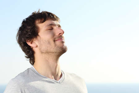 Photo for Close up of a man doing breath exercises outdoor with the sky in the background                - Royalty Free Image