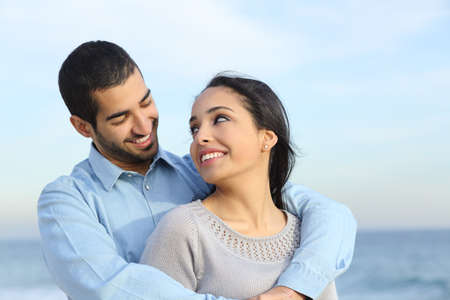 Photo pour Arab casual couple cuddling happy with love on the beach with the horizon and the sea in the background                - image libre de droit