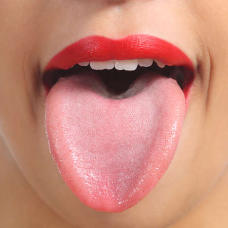 Foto de Close up of a front view of a woman tongue and red painted lips         - Imagen libre de derechos