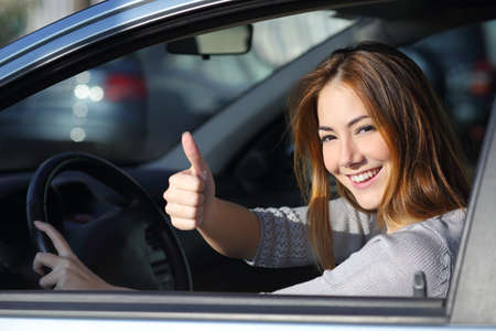 Photo for Happy woman inside a car driving in the street and gesturing thumb up - Royalty Free Image