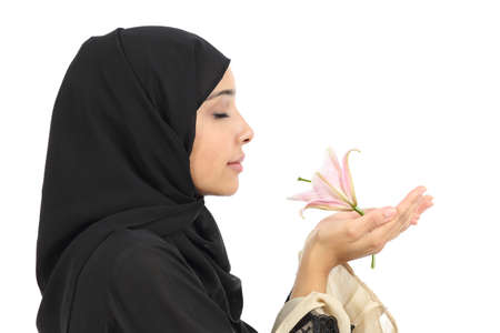 Foto de Close up of a profile of an arab woman smelling a flower isolated on a white background - Imagen libre de derechos