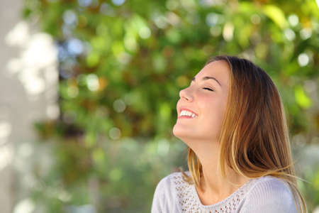 Photo pour Young happy smiling woman doing deep breath exercises outdoor with a green background            - image libre de droit