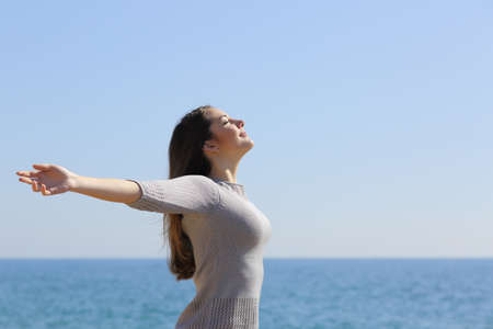 Foto de Happy relaxed woman breathing deep fresh air and raising arms on the beach with the horizon in the background - Imagen libre de derechos