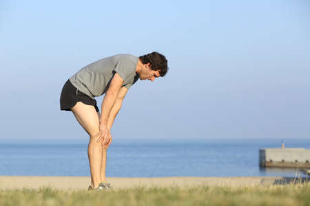 Photo pour Exhausted runner man resting on the beach after workout with the ocean in the background               - image libre de droit
