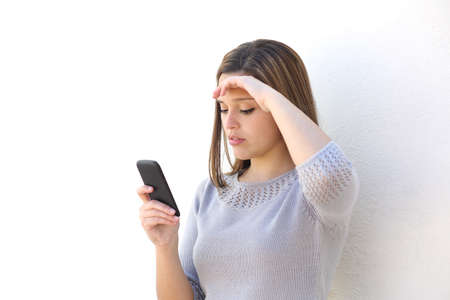 Foto de Worried woman looking at the mobile phone on a white wall isolated           - Imagen libre de derechos