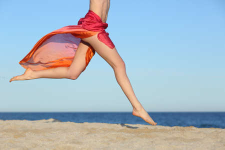 Photo pour Woman legs jumping on the beach happy with the horizon and sea in the background             - image libre de droit