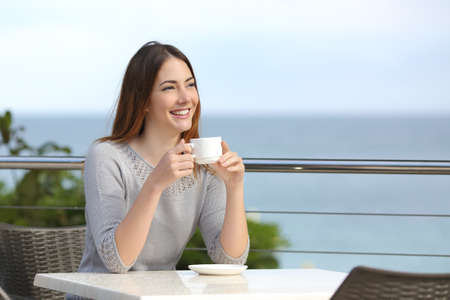 Beautiful woman holding a cup of coffee in a restaurant with the sea in the background