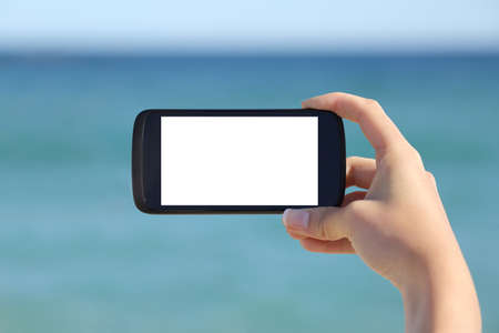 Photo pour Woman hand showing a blank smart phone horizontal screen display on the beach with the sea in the background           - image libre de droit