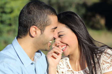 Photo pour Arab casual couple man and woman flirting and laughing happy in a park with a green  - image libre de droit